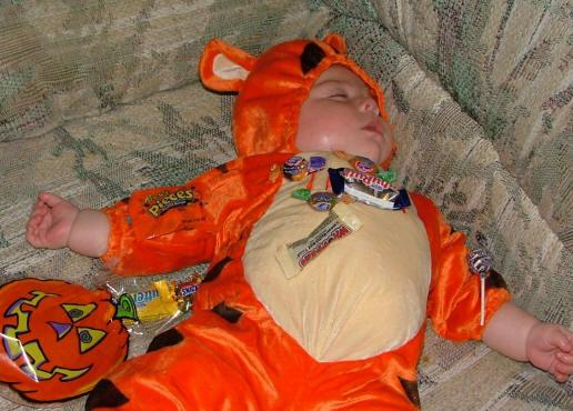 bebé dormido con muchos dulces, disfrazado de Tiger