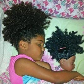 niña de cabello negro chino dormida con una muñeca que se le asemeja