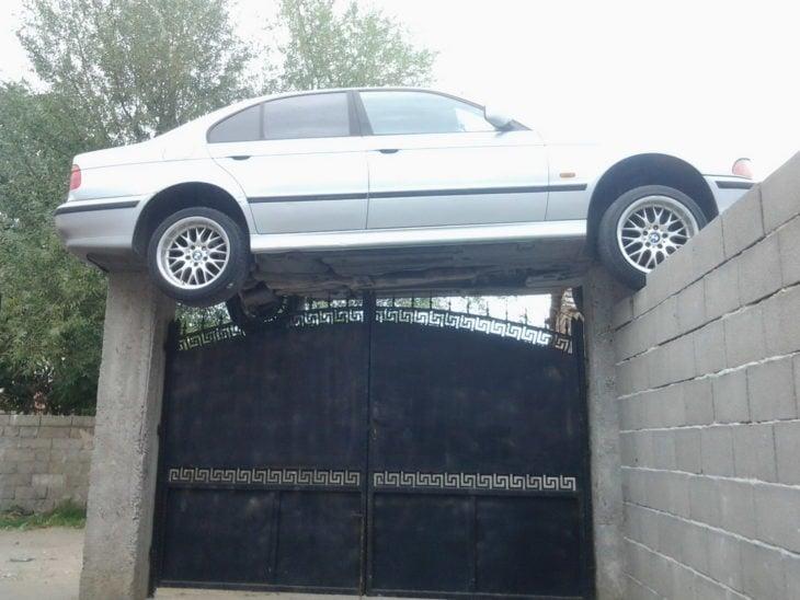 """Fotos sin explicación. Un carro está """"estacionado"""" encima de un portón"""