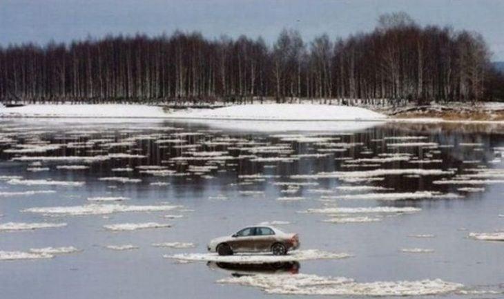 Fotos sin explicación. Un carro flotando en un río sobre una parte del lago congelado