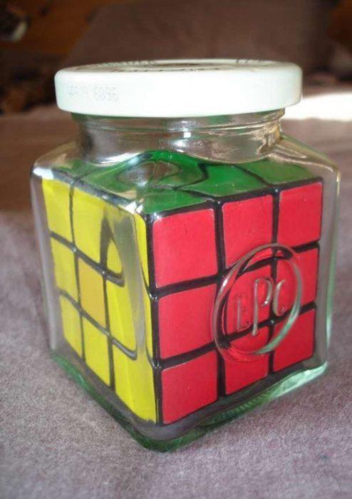 Fotos sin explicación. Un cubo de rubric adentro de un jarrón con tapa redonda más chico que el mismo cubo