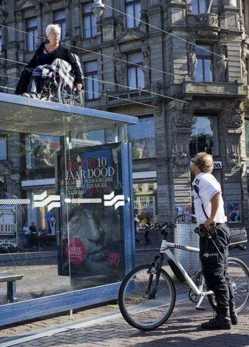 Fotos sin explicación. Una señora encima de ruedas en el techo de la parada de autobuses