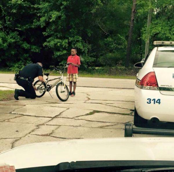 policia arreglando bicicleta de niño