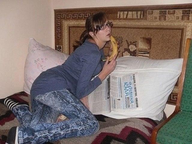 Chica en cama posando con un plátano en la boca
