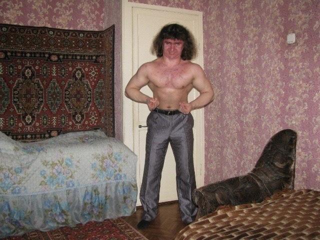 Hombre sin camiseta haciendo flexión en habitación tapizada