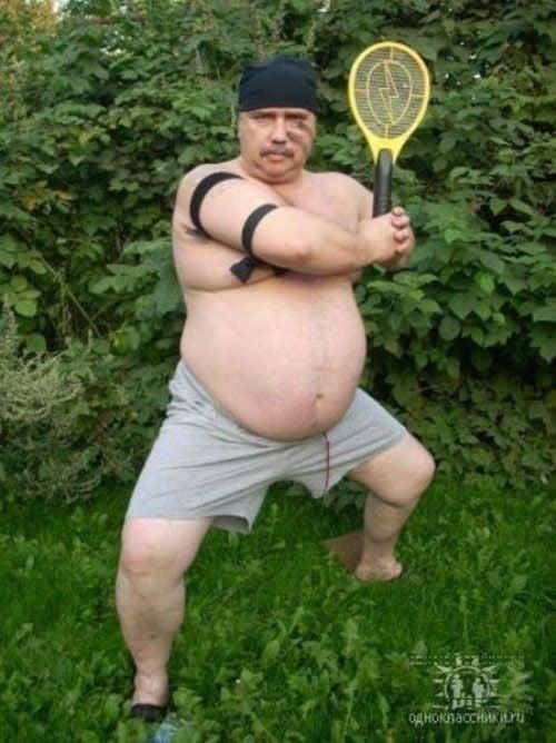Hombre obeso posando con las piernas abiertas con una raqueta en la mano