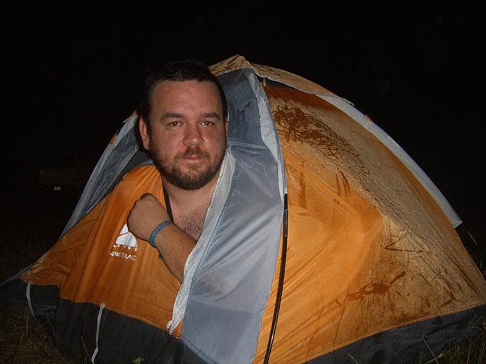 Un hombre adulto en una casa de campaña enla que no cabe