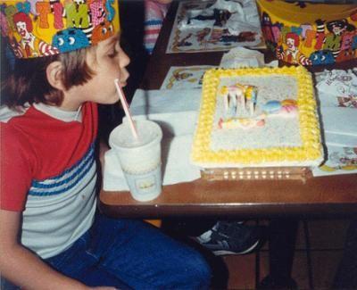 Niño soplando las velitas en su pastel de cumpleaños