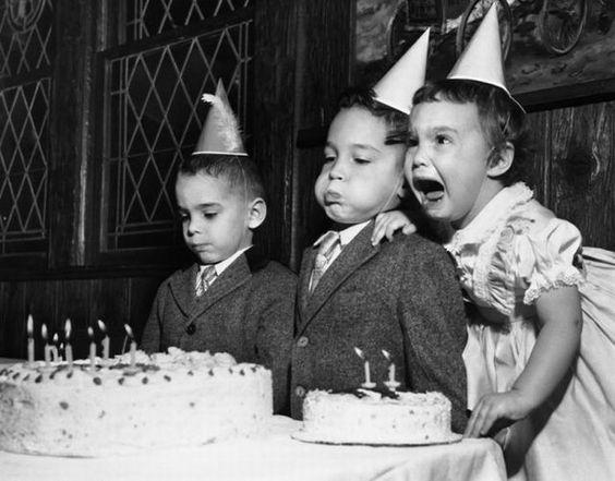 Tres niños frente a dos pasteles de cumpleaños, uno con cara de tristeza, otro soplando las velitas y una más llorando