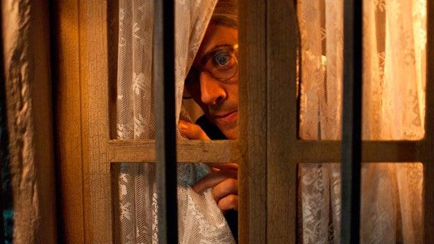 hombre asomándose discretamente por la ventana
