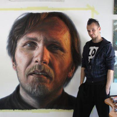 Dino Tomic artista noruego con una de sus pinturas