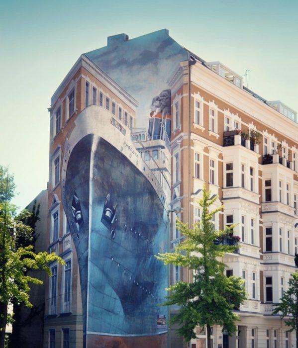 Graffitti en un edificio que asemeja un barco pasando entre dos edificios