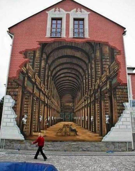 Graffitti en un edificio que hace parecer que hay un hoyo en la pared y se logra ver un pasadizo como de una libreria