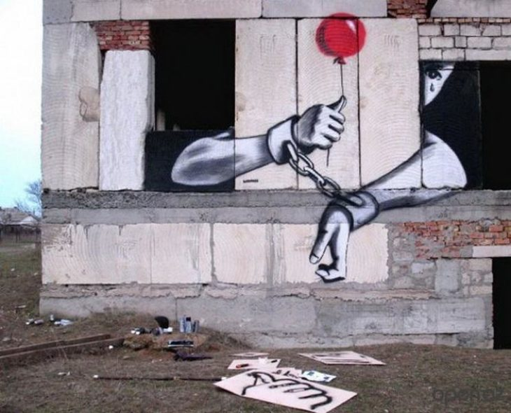 Graffitti de un niño con las manos atadas asomándose por una ventana