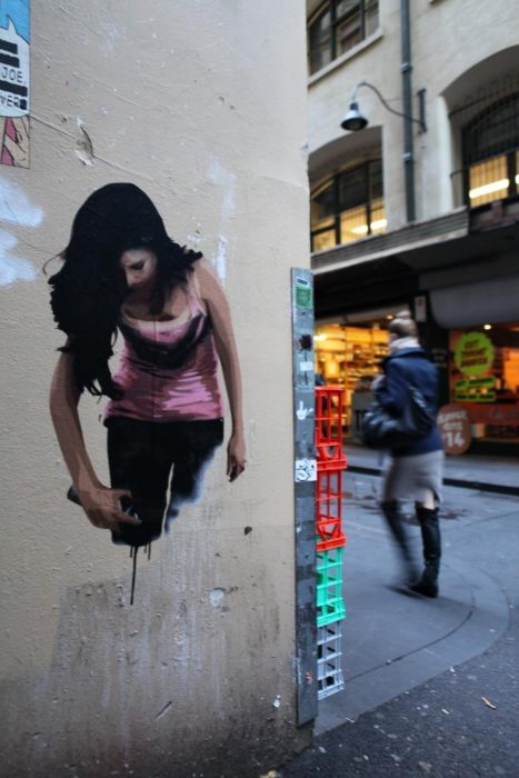 Graffitti de una mujer pintándose a si misma