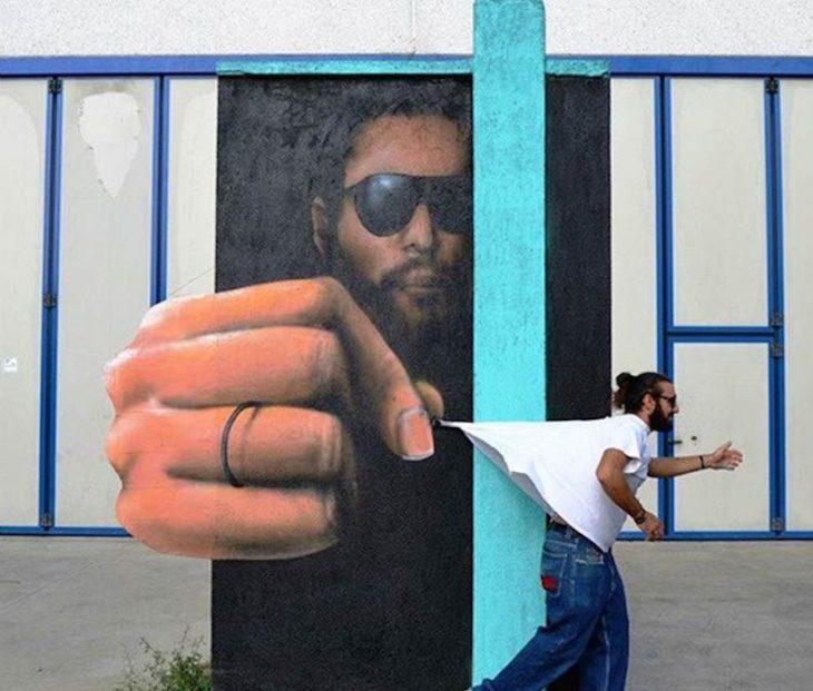 Graffitti de un hombre en el fondo que saca la mano con el puño cerrado