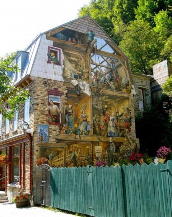 Graffitti de muchas personas en el costado de una casa
