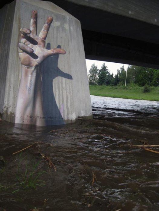 Graffitti de una mano que brota de del agua