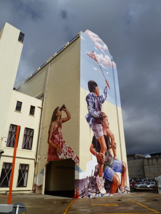 Graffitti de tres niños atrapando nubes