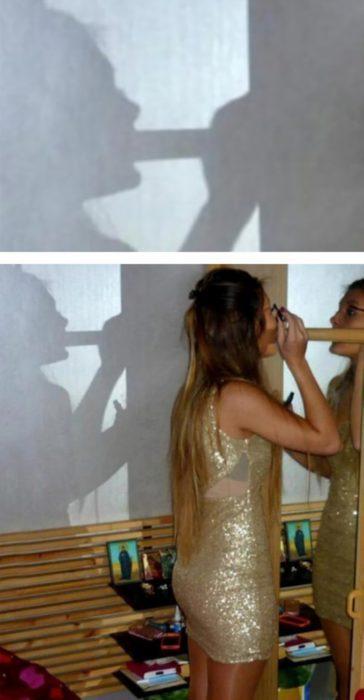 Fotos recortadas: Una mujer está maquillándose frente al espejo, pero al ver su sombra parece otra cosa