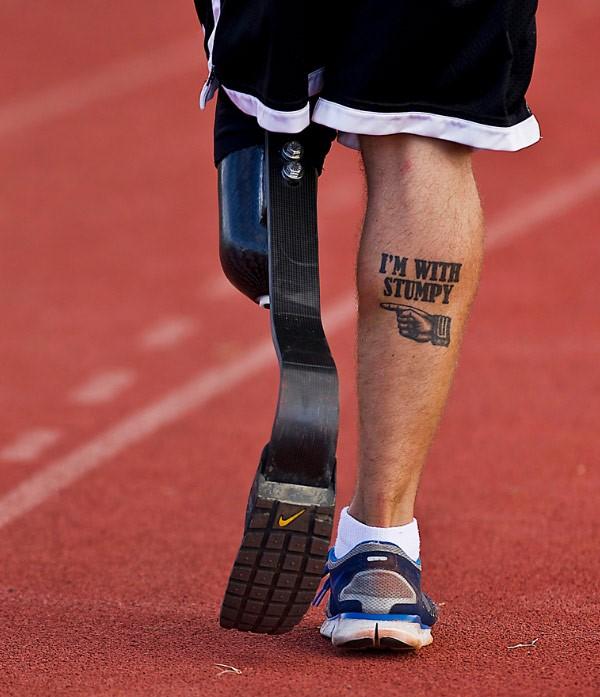 Hombre con una pierna y una prótesis, en la pierna trae un tatuaje que dice I'M WITH STUMPY
