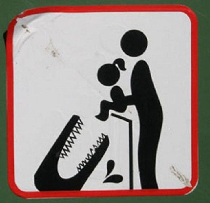 Señal de un cocodrilo a punto de comerse a una niña