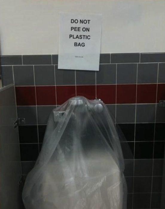 Letrero encima de un retrete cubierto de plástico que dice que no orinen en él