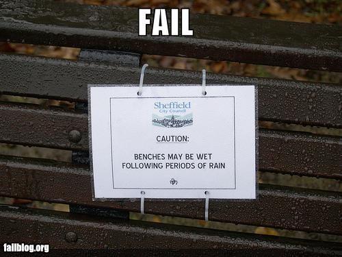 Letrero en un banco que dice que si ha llovido pueden estar mojadas las bancas