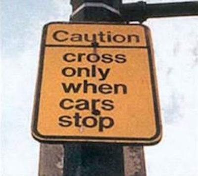 Señalamiento que advierte de no cruzar la calle hasta que los carros se detengan