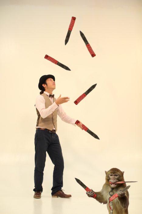 mono haciendo malabares con cuchillos junto a malabarista