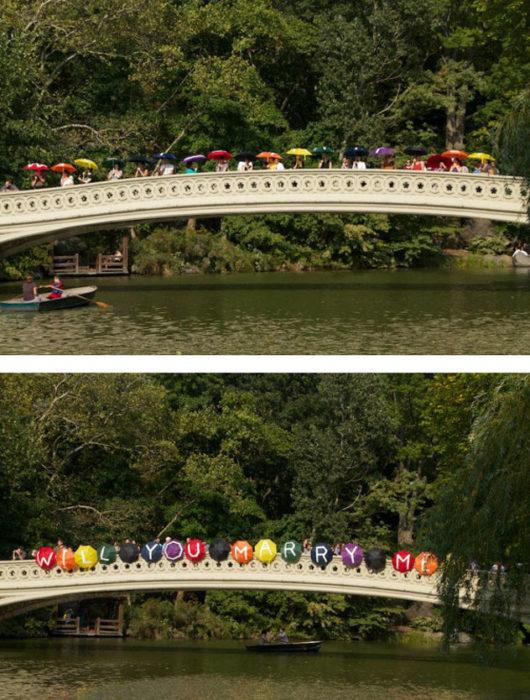 Propuesta. Novios van en una lancha y cuando pasan por un puente con paraguas escrito está que si quiere casarse con él