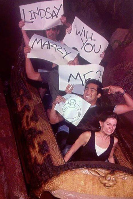 Propuessta: En un juego mecánico la foto que sale es la chica al frente, cuatro hombres atrass, cada uno sosteniendo un letrero que dice Lindsay will you marry me?