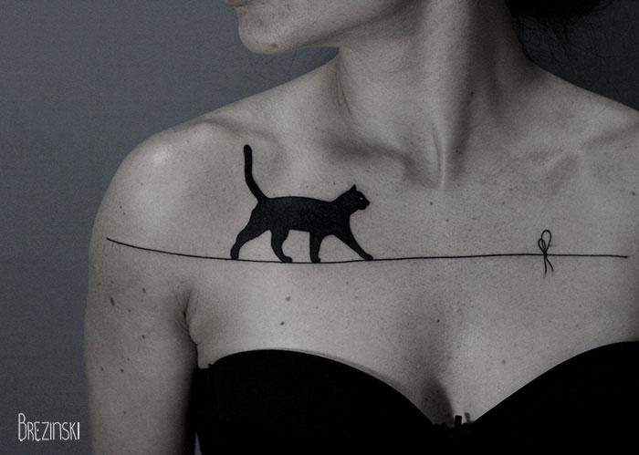 tatuaje de gato negro caminando sobre hilo en pecho de mujer