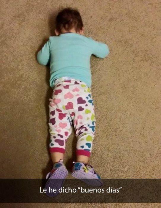 Bebé acostado sobre alfombra beige, bocabajo