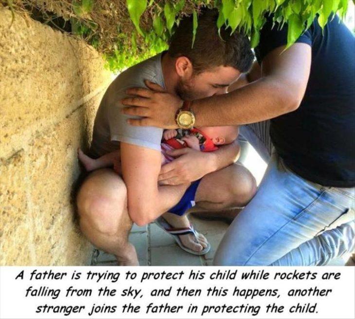 extraño cubre a padre que a su vez cubre a su bebé