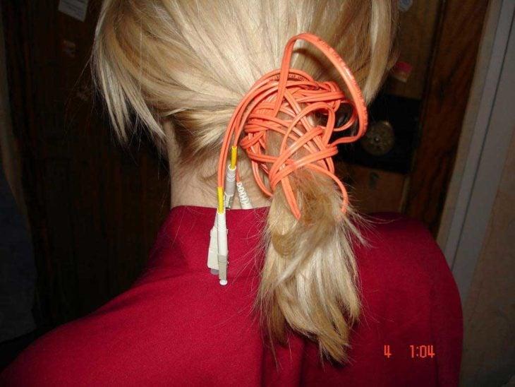 mujer se hace una coleta de caballo con un cable
