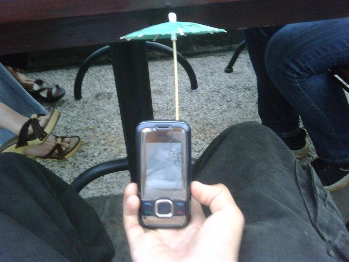 celular con una sombrillita de bebidas