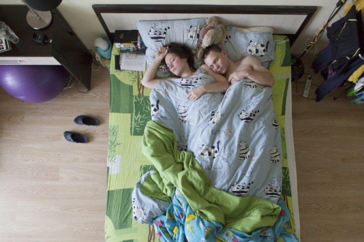 pareja de embarazados durmiendo, las sábanas son verdes