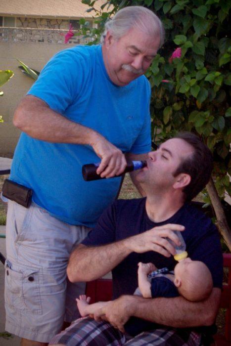 padre dando cerveza a su hijo que a su vez da biberón a su hijo