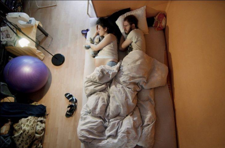 un hombre que cuida de su esposa embarazada mientras están durmiendo