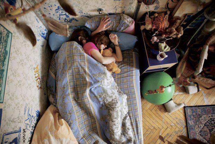 pareja de embarazados dormidos con un oso de peluche