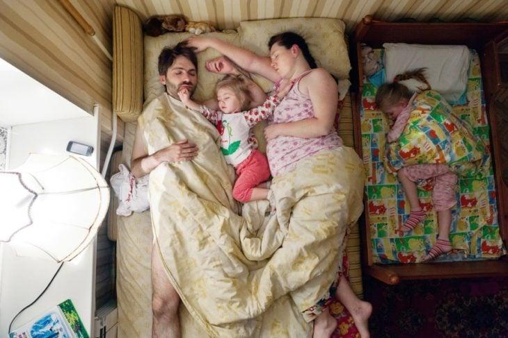 pareja de embarazados con su hija pequeña durmiendo