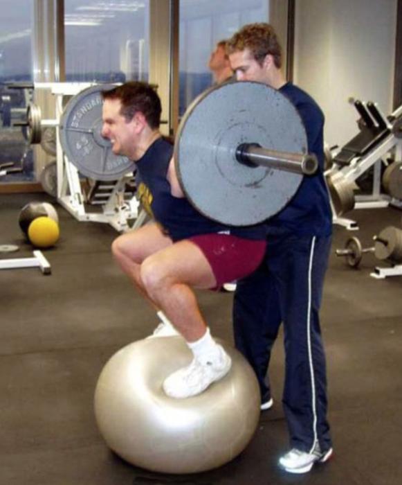 hombre haciendo pesas sobre una pelota de yoga