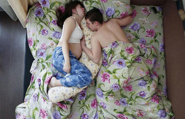pareja de embarazados, sábanas de flores