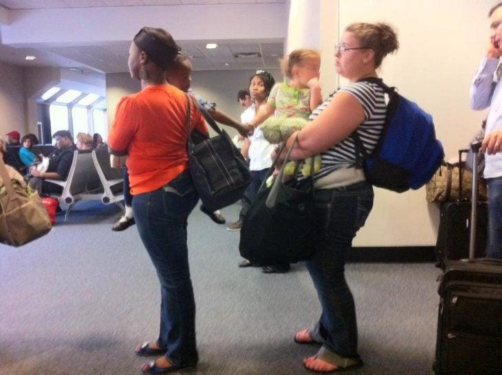 dos niñas en los brazos de sus madres que se toman las manos
