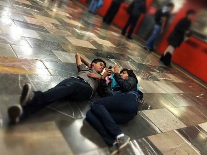 jovenes acostados mientras esperan el metro