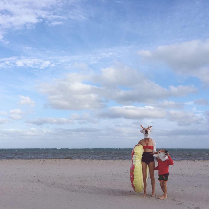 personas con cabezas de ciervo en la playa