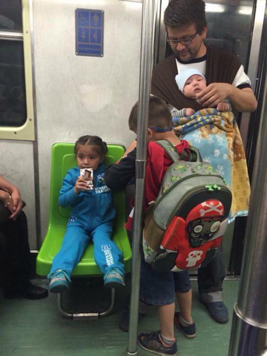 hombre con sus hijos en el metro