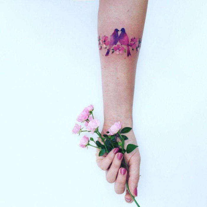 tatuaje de flor en un brazo y una mano sosteniendo una real