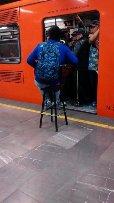persona carga su propio asiento al metro